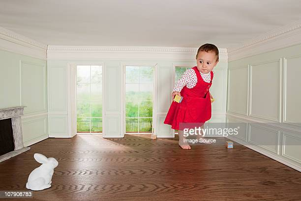 Toddler girl in a tiny room, looking at rabbit