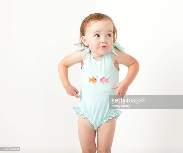 Toddler girl in bathing suit shrugging shoulders.