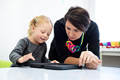 Toddler girl in child occupational therapy session doing playful exercises on a digital tablet with her therapist.