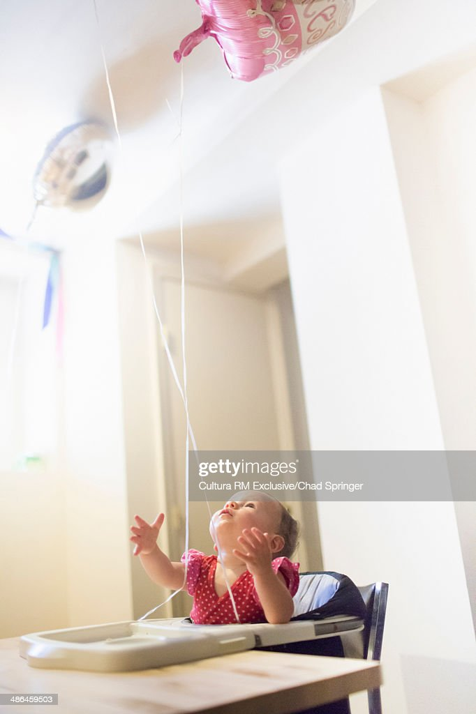 Toddler girl in highchair looking up at balloons : Stock Photo