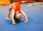 Children can excel at gymnastics, even beginning at a very young age! This toddler girl, aged 4, is demonstrating a Bridge position by pushing off her hands and feet and thrusting her back upwards. Sh
