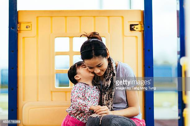 Toddler girl kissing mom's cheek in the playground