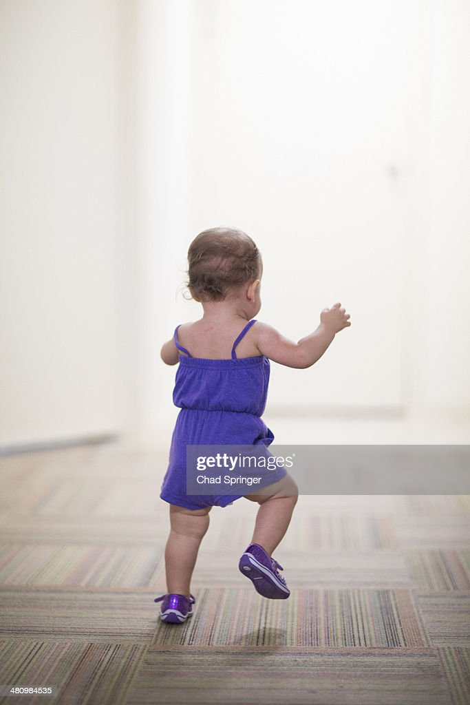 Toddler girl learning to walk : Stock Photo