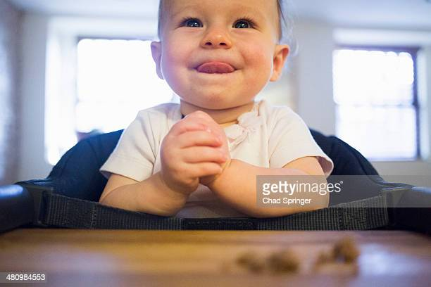 Toddler girl licking lips in highchair