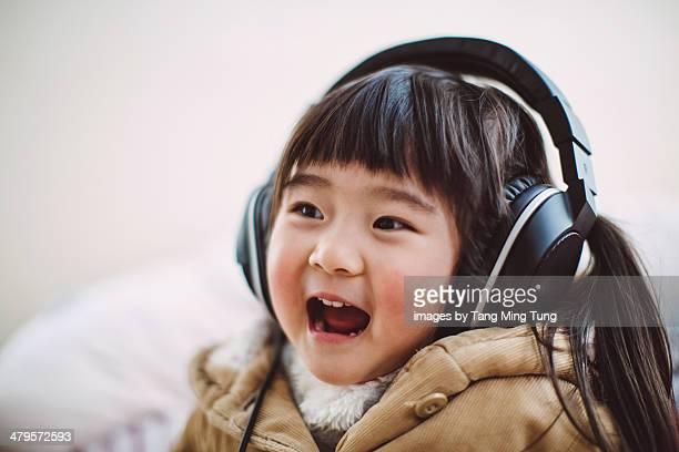 Toddler girl listening to music joyfully