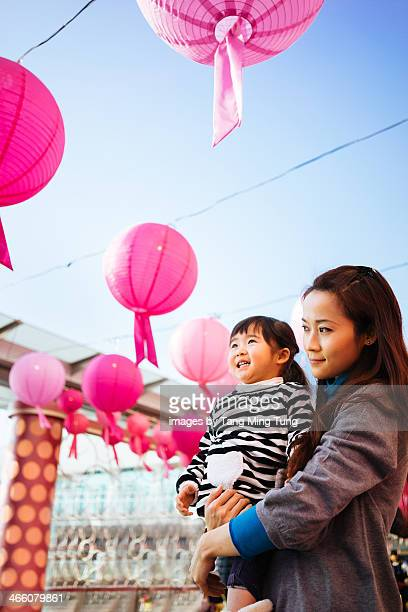 Toddler girl looking at Chinese lanterns with mom
