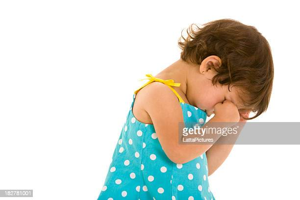 Toddler girl looking away and rubbing her eyes