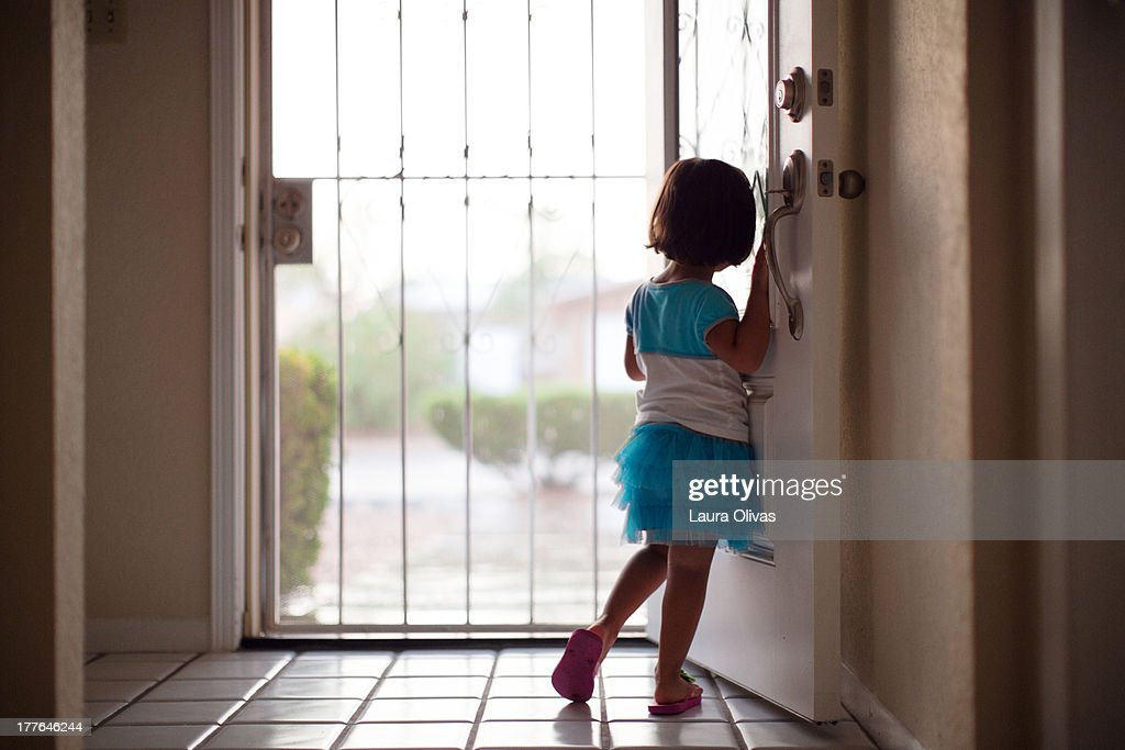 Toddler girl looking out front door : Stock Photo