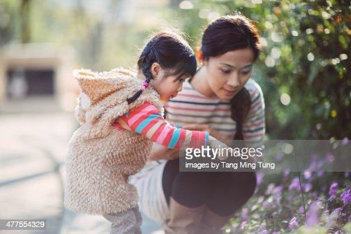 Toddler girl & mom admiring flowers in the park