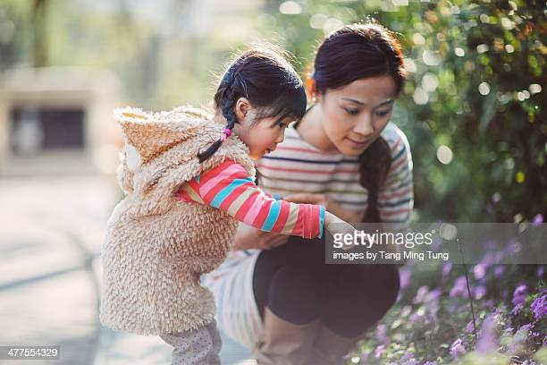 Toddler girl & mom admiring flowers in the park