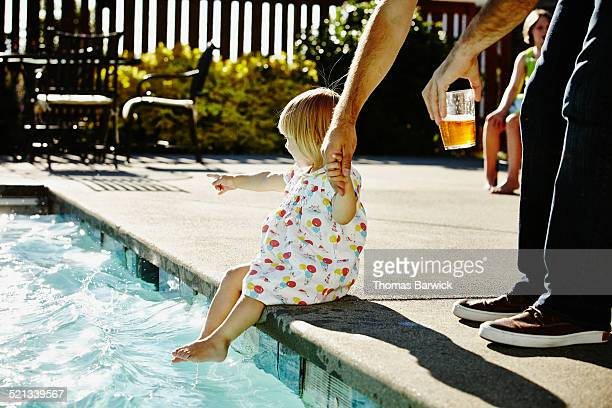 Toddler girl on edge of pool holding fathers hand