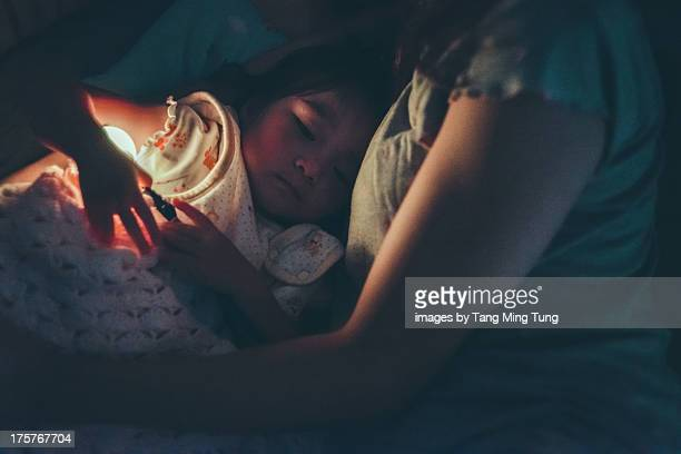 Toddler girl on the bed ready to sleep with mom