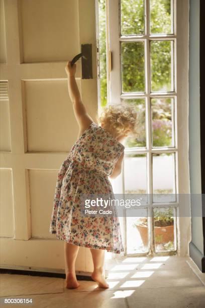 Toddler girl opening front door
