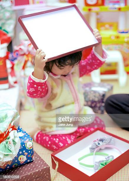 Toddler girl opens a present on Christmas morning