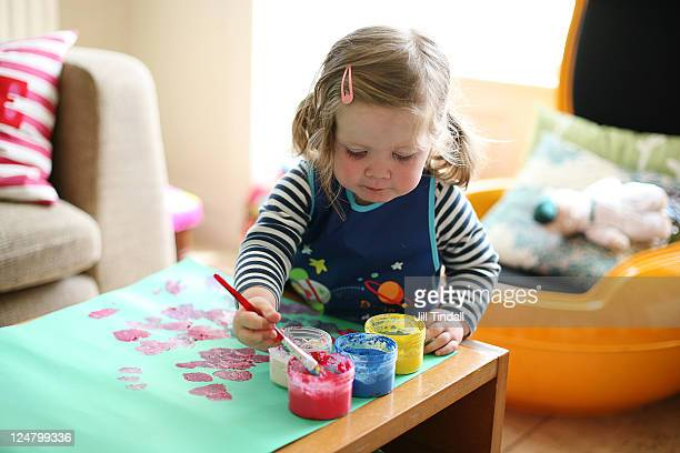 Toddler girl painting at home