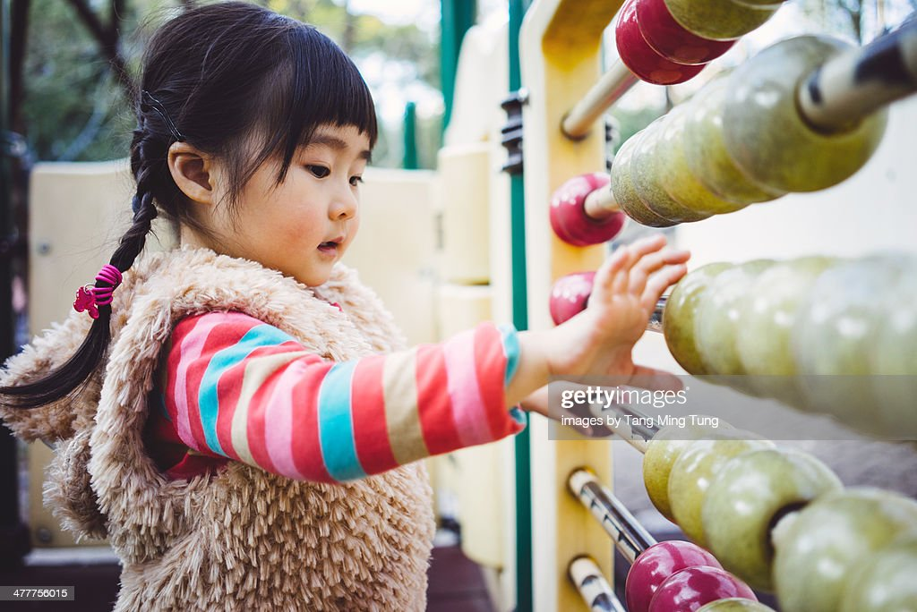 Toddler girl playing abacus in playground