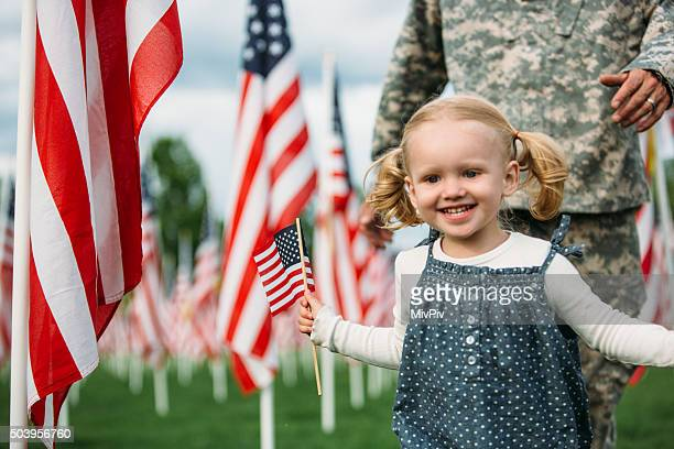 Toddler girl playing happily with an American Soldier in uniform