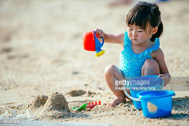 Toddler girl playing in the sand on the beach