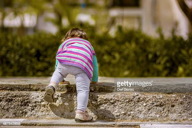 Toddler girl playing on concrete stairs
