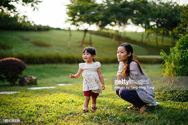 Toddler girl playing on the lawn with mom