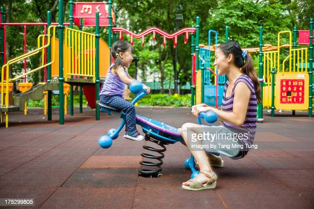 Toddler girl playing seesaw with young mom