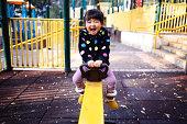 Toddler girl playing the seesaw joyfully