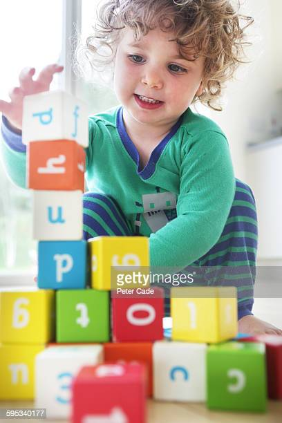 Toddler girl playing with coloured alphabet bricks