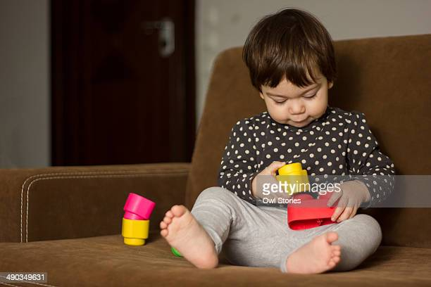 Toddler girl playing with construction blocks