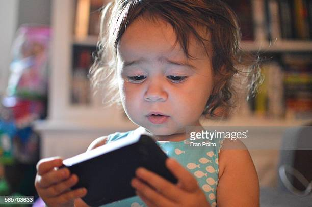 Toddler girl playing with smart phone
