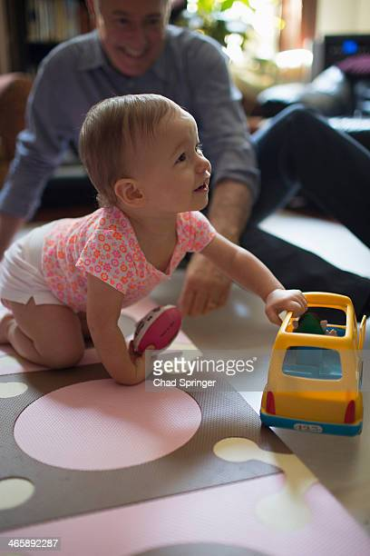 Toddler girl playing with toy car