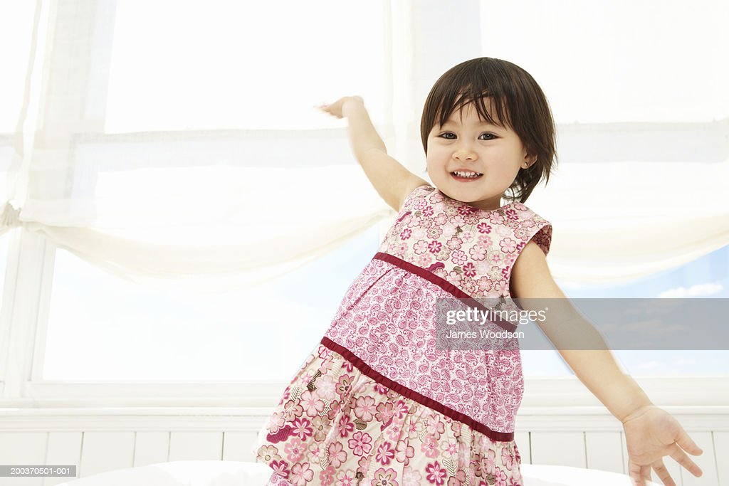 Toddler girl (21-24 months)posing on bed, portrait, close-up