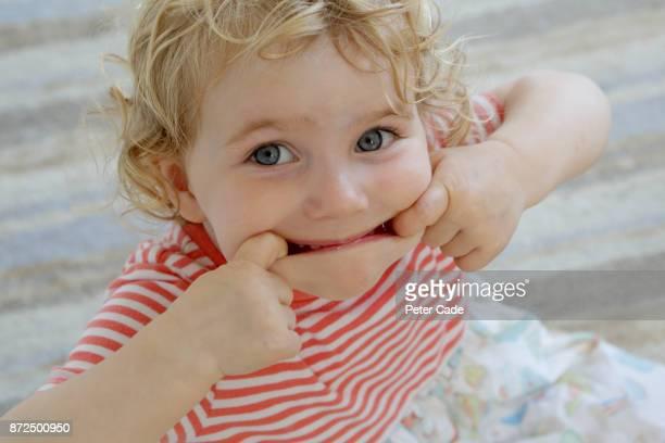 Toddler girl pulling face at camera