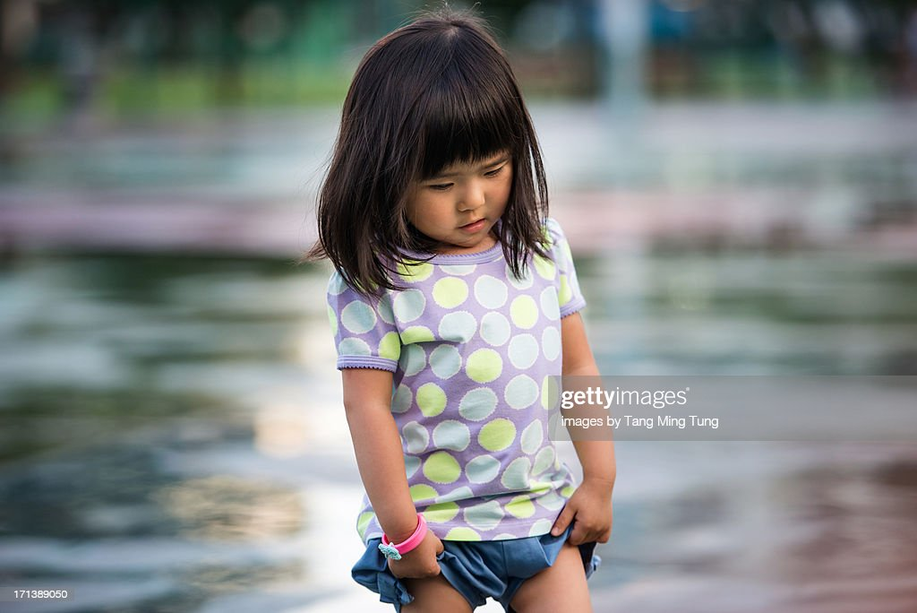 Toddler girl pulling up her shorts. : Stock Photo