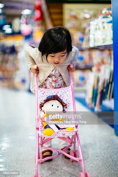 Toddler girl pushing a toy stroller in toy shop