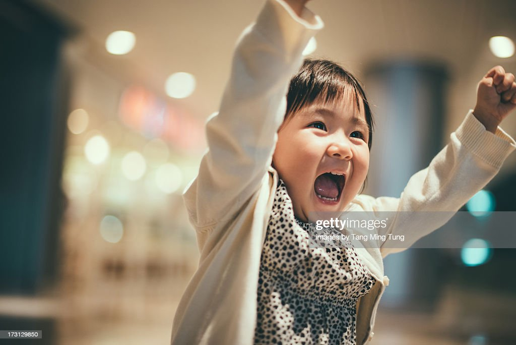 Toddler girl raising arms in the air laughing : Stock Photo