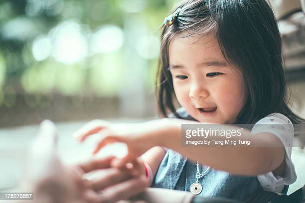 Toddler girl reaching out her hand touching daddy
