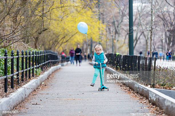 Toddler girl riding a scooter in Central Park