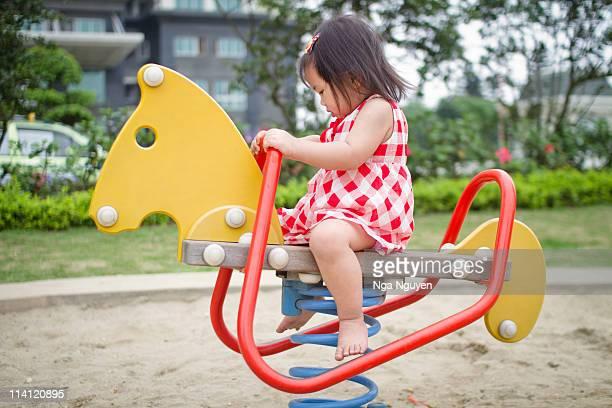 Toddler girl riding horse in  playground