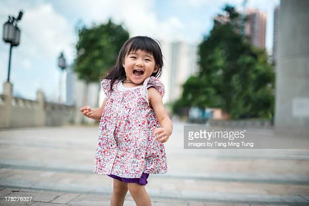 Toddler girl running towards camera joyfully.