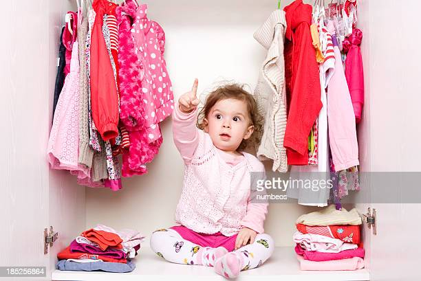 Toddler girl sitting in closet with red and pink clothes