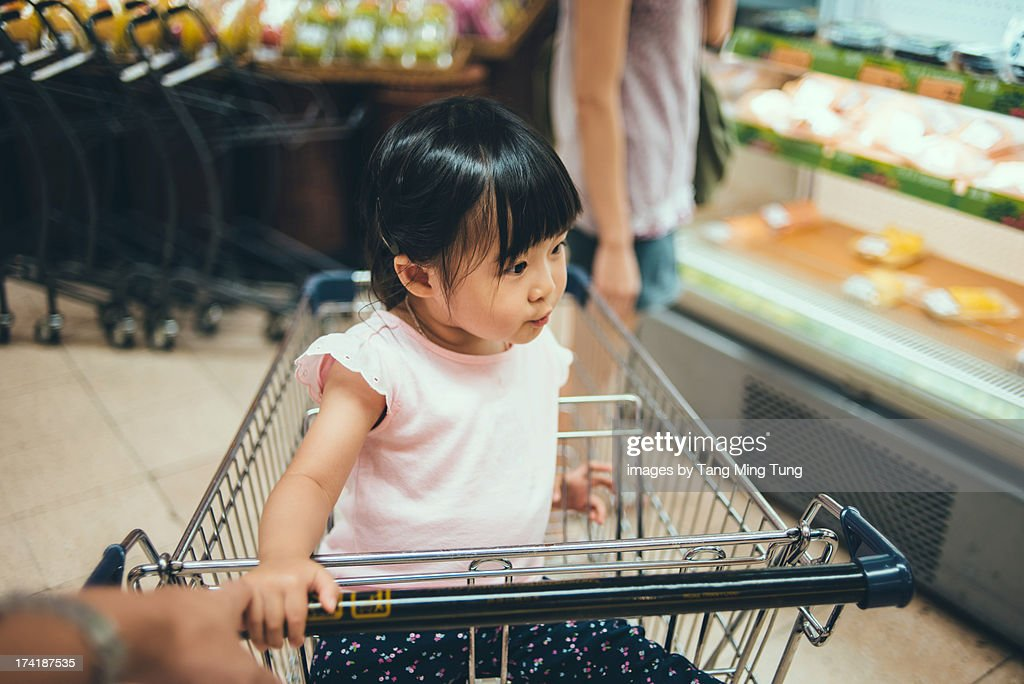 Toddler girl sitting in trolley in supermarket : Stock Photo