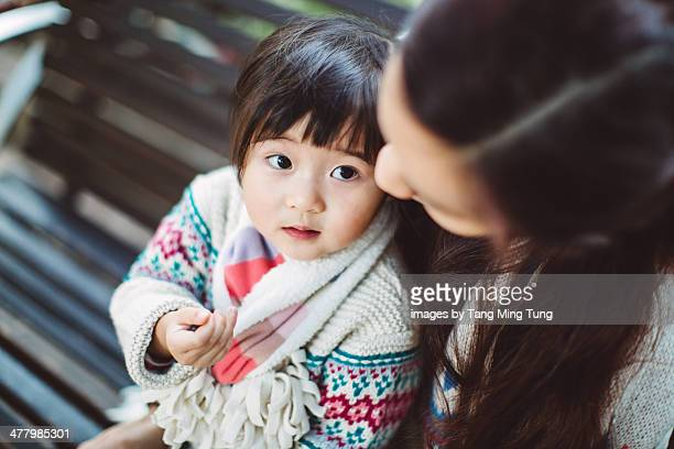 Toddler girl sitting on bench with mom in the park