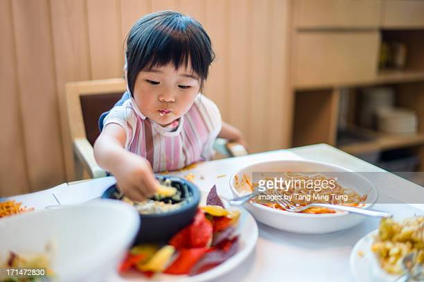 Toddler girl sitting on highchair having spaghetti