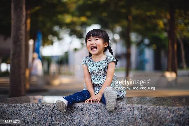 Toddler girl sitting on stone bench laughing