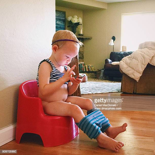 Toddler girl sitting on training toilet while using a smartphone