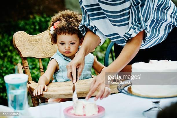 Toddler girl sitting watching mother cut cake