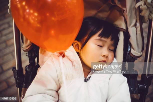 Toddler girl sleeping soundly in the stroller