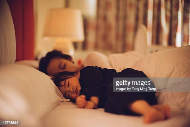 Toddler girl sleeping soundly on the bed with mom