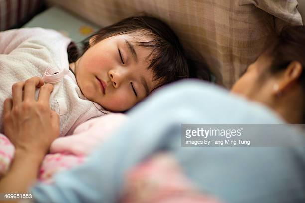 Toddler girl sleeping soundly with mom on bed