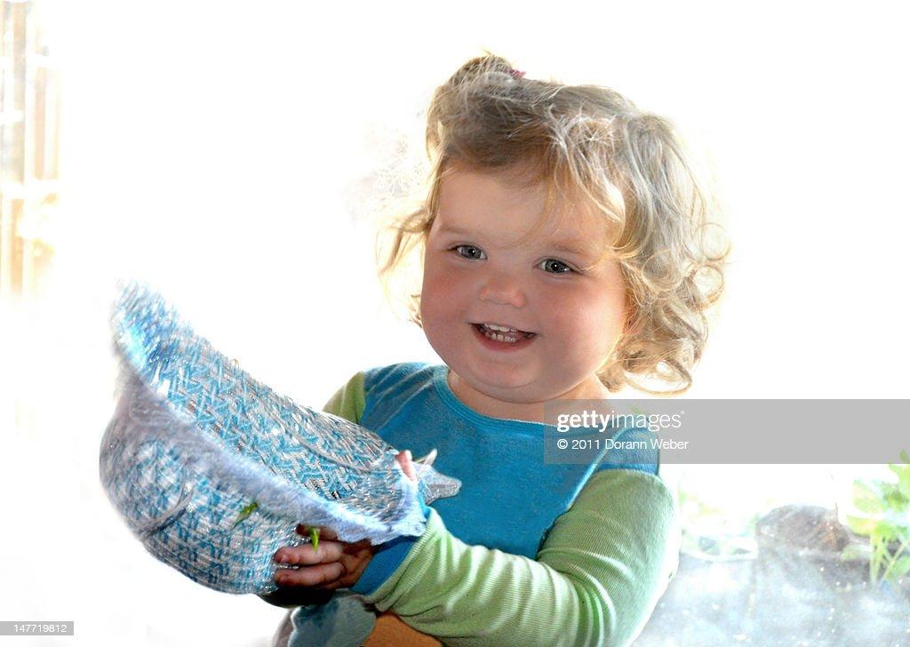 Toddler girl smiles holds hat : Stock Photo